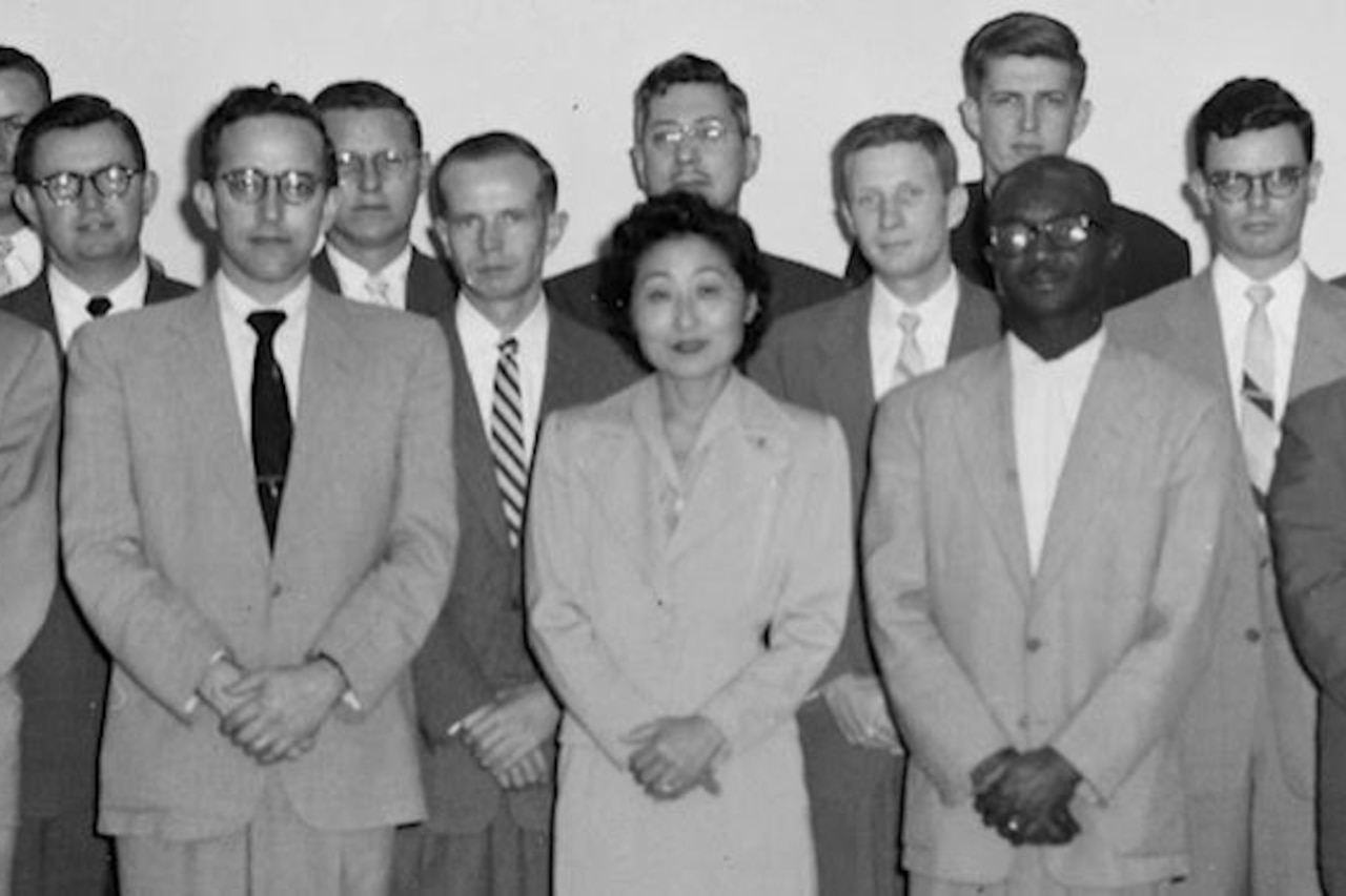 A group of men and one woman, all in business suits, pose for a photo.