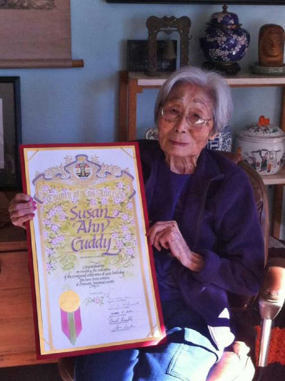 """A woman holds up a plaque that says """"Susan Ahn Cuddy."""""""