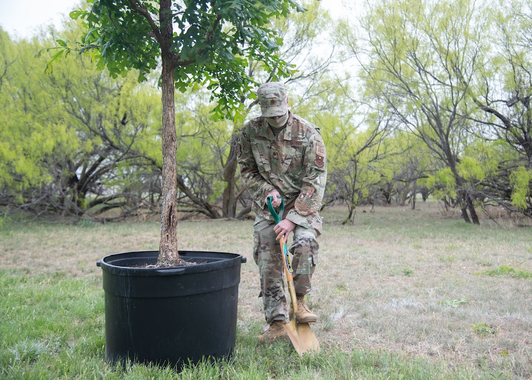 """U.S. Air Force Maj. Christopher Higgins, 17th Civil Engineer Squadron commander, breaks ground to plant a Bur Oak tree on Goodfellow Air Force Base, Texas, April 21, 2021. This tree was planted for Earth Day 2021's theme of """"Restore Our Earth"""", which focuses on innovative thinking that can improve the world's ecosystems. (U.S. Air Force photo by Staff Sgt. Tyrell Hall)"""