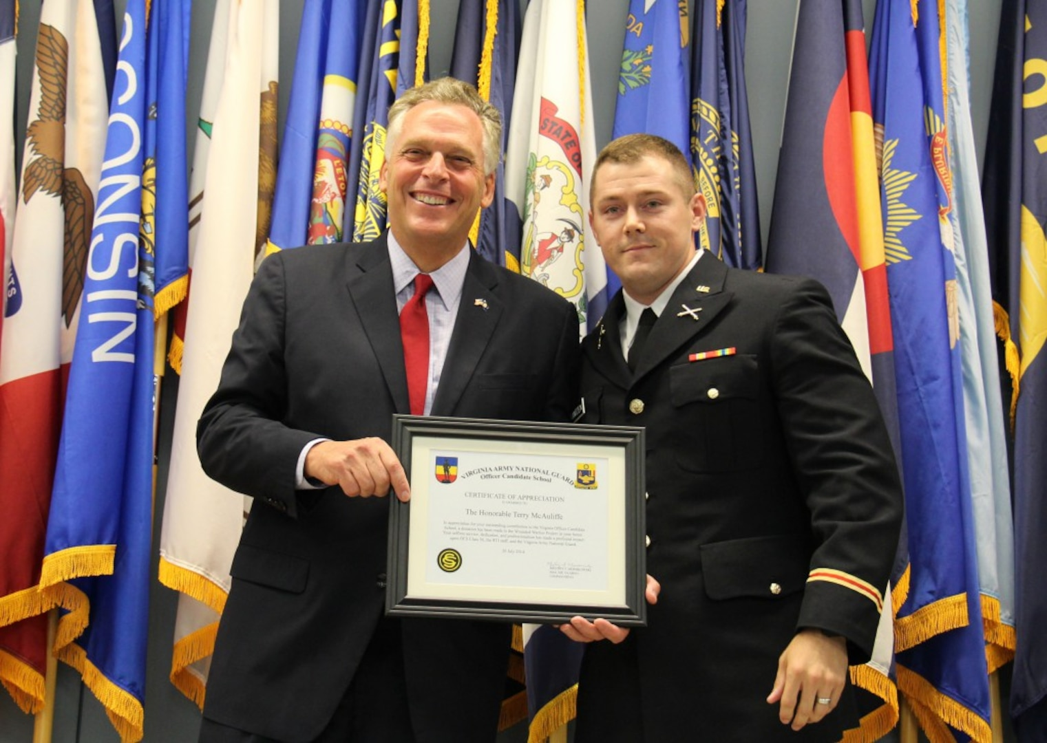 Second Lt. Daniel K. Frantzen presents Governor Terry McAuliffe with a certificate of appreciate for serving as the guest speaker for Officer Candidate School Class 56 July 26, 2014, at the 183rd Regiment, Regional Training Institute at Fort Pickett, Va.