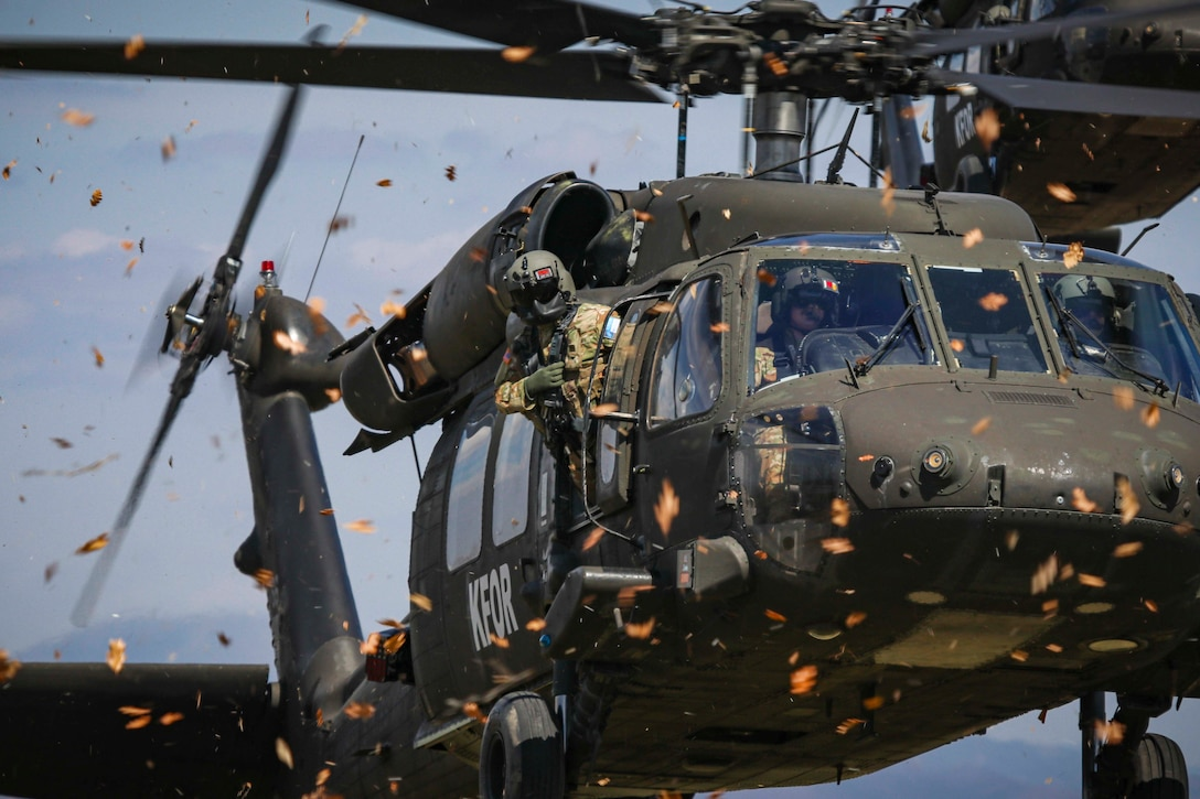 A soldier looks out the side of a helicopter in midair.