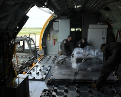 Members of the 756th Air Refueling Squadron load a pallet of laptops onto a KC-135 Stratotanker April 21, 2021, at Joint Base Andrews, Md. The squadron was tasked with delivering the laptops to The Bahamas as part of the Denton Program humanitarian mission. (U.S. Air Force photo by Staff Sgt. Cierra Presentado/Released)