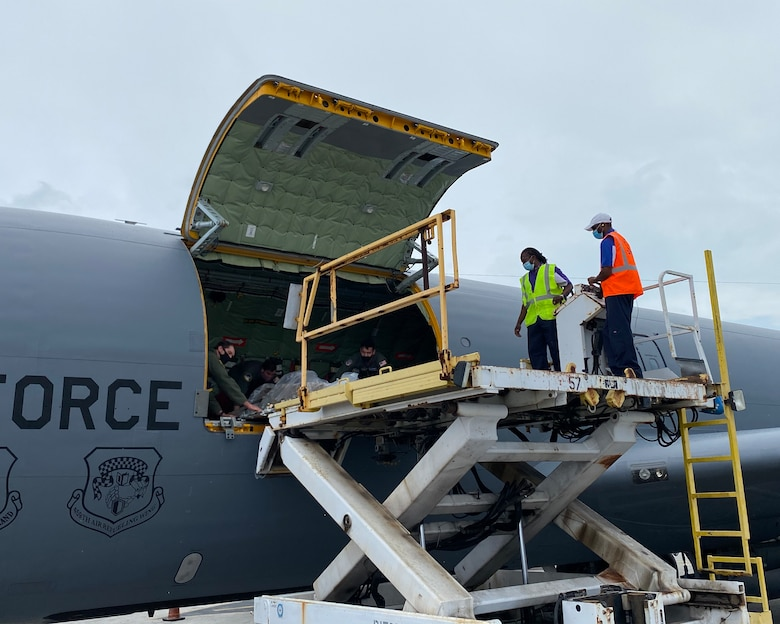 Crew members from the 756th Air Refueling Squadron assist Bahamian airport officials with unloading 100 laptops from a KC-135 Stratotanker as part of the Denton Program humanitarian mission April 23, 2021, in The Bahamas. The mission will aid The Bahamas in recovery efforts after the island was struck by Hurricane Dorian in 2019 leaving many schools, homes and business destroyed. (Courtesy photo)
