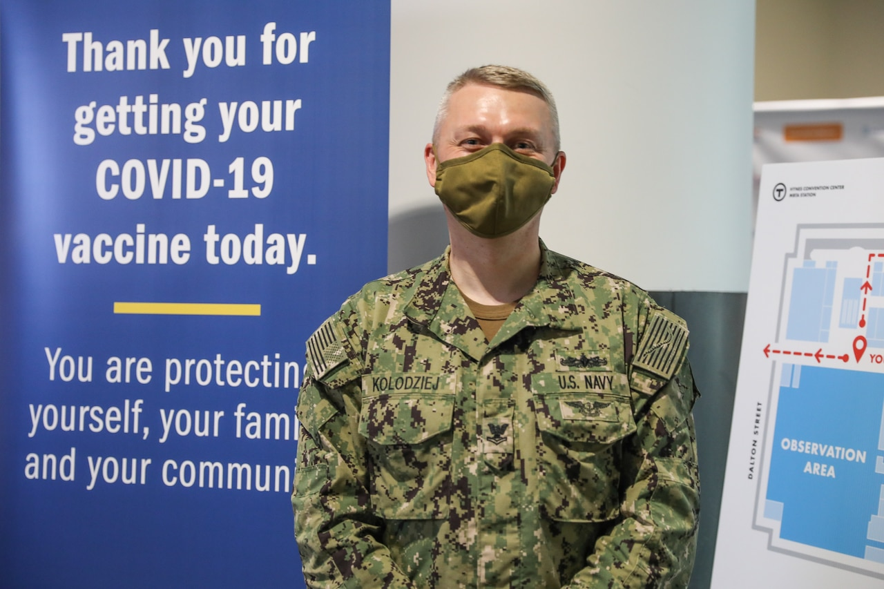 A sailor wearing a face mask poses in front of a COVID-19 vaccination banner.