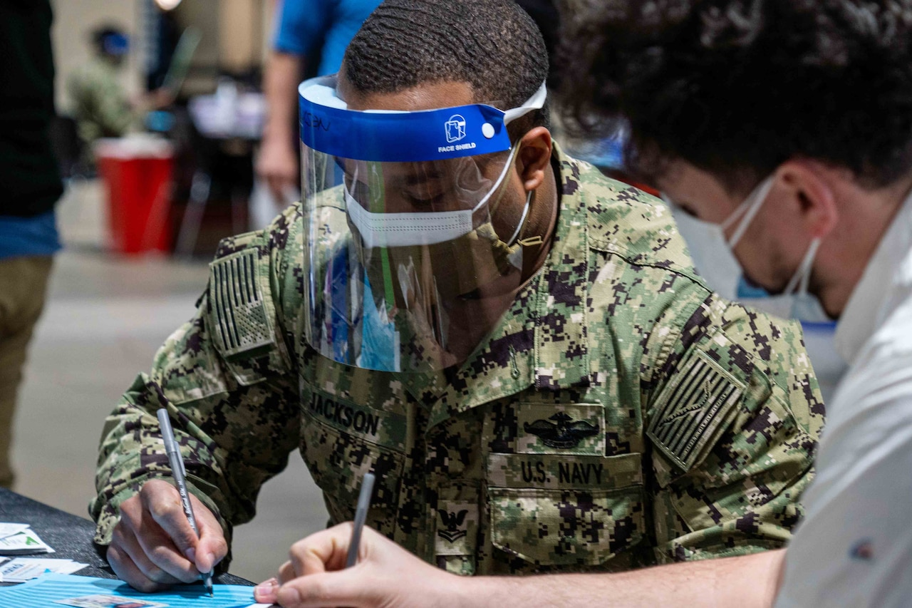 A sailor wearing a face mask documents info for a vaccine.