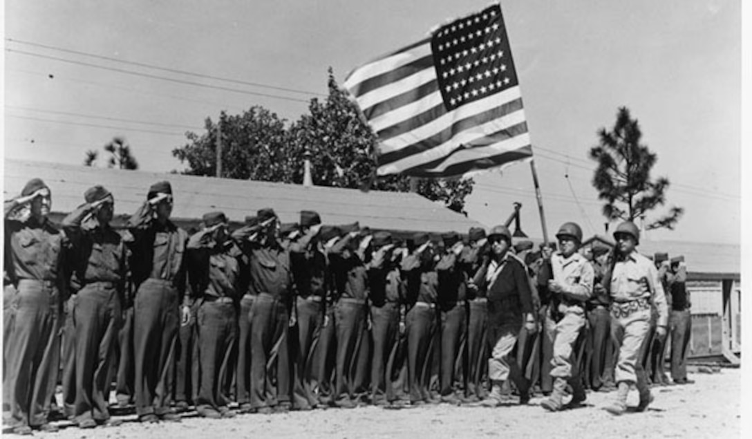 Men in uniform salute as three men walk by carrying a U.S. flag.