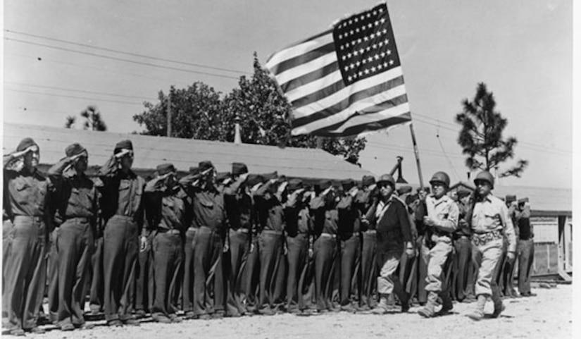 Men in uniform salute as three men walk by carrying a U.S. flag.