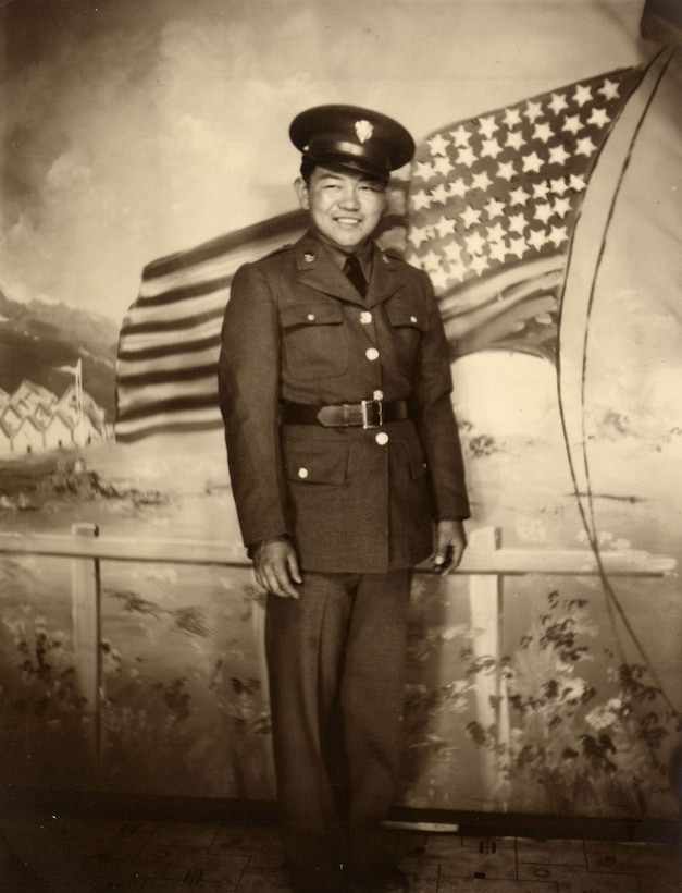 A man in uniform poses in front of a painting of a U.S. flag.