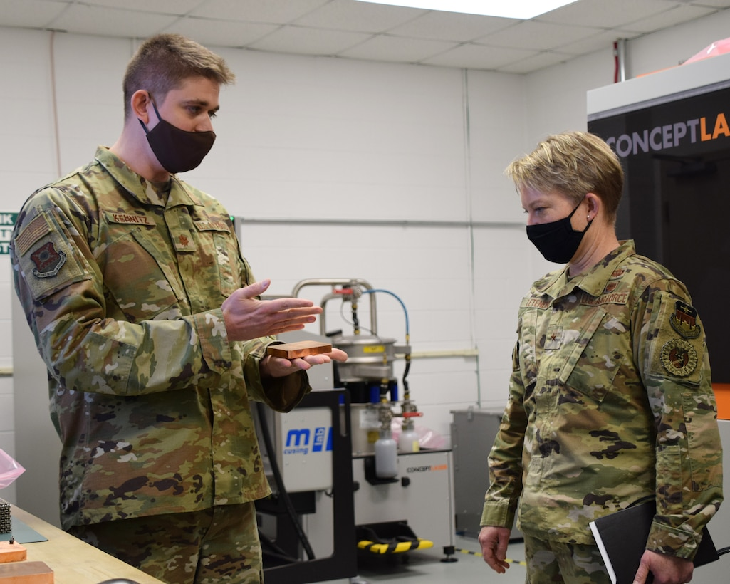 Maj. Ryan Kemnitz, assistant professor of astronautical engineering, describes AFIT's additive manufacturing 3D printer process to Brig. Gen. Linell Letendre, dean of faculty, USAFA.  The state-of-the-art system uses a laser to melt a finely graded metal powder, layer by layer, to digitally fabricate aerospace metal parts.
