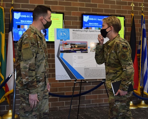 Capt. Aron Wing discusses his research on modeling high speed pin-on-disk experiment with Brig. Gen. Linell Letendre, dean of faculty, USAFA. Capt. Wing graduated from AFIT in 2021 with a master's of science degree in applied mathematics.