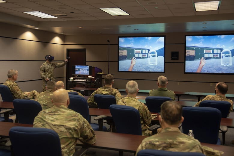 U.S. Air Force Staff Sgt. Matthew Reinitz, 423rd Mobility Training Squadron Aerial Port Expeditor instructor, explains how aerial porters utilize simulators for training to Total Force Mobility Air Forces (TF MAF) leadership during Total Force Phoenix Rally, April 21, 2021, at the U.S. Air Force Expeditionary Center headquarters on Joint Base McGuire-Dix-Lakehurst, New Jersey. U.S. Air Force Expeditionary Operations School instructors were given the opportunity to showcase their contributions to leadership throughout TF MAF. (U.S. Air Force photo by Master Sgt. Ashley Hyatt)