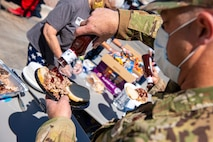 Male Airman puts barbecue sauce on his pulled pork sandwich.