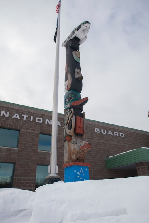 The honor pole that was built by George and James Bennett, a father-son duo from Sitka, sits in front of the Alaska Army National Guard armory April 1, 2021, days before it is restored. The pole is a momument that was built in 2007 and 2008, and is dedicated to the profound contributions of the Alaska Natives to the safety and heritage of the state in the past and present. (U.S. Army National Guard photo by Spc. Grace Nechanicky)