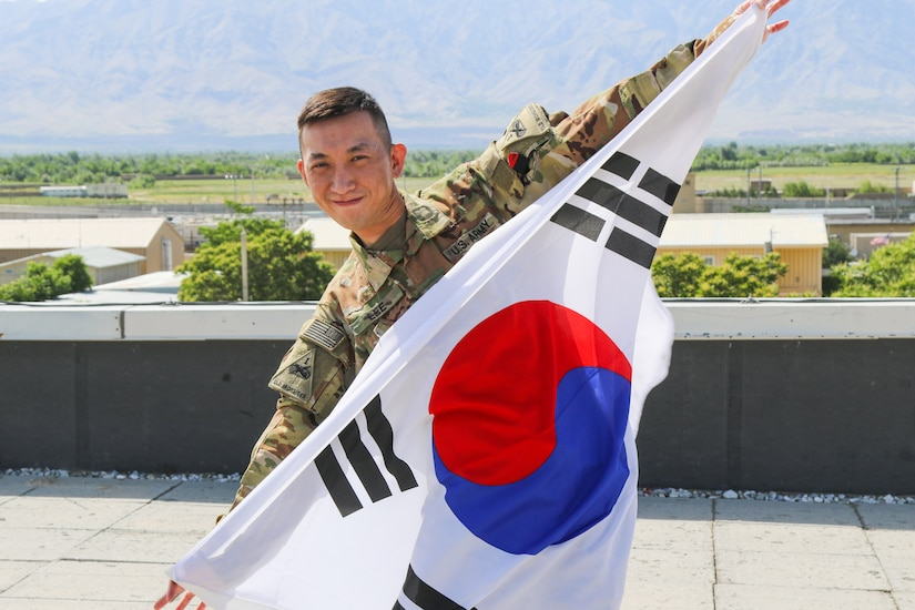 A soldier holds up a South Korean flag.