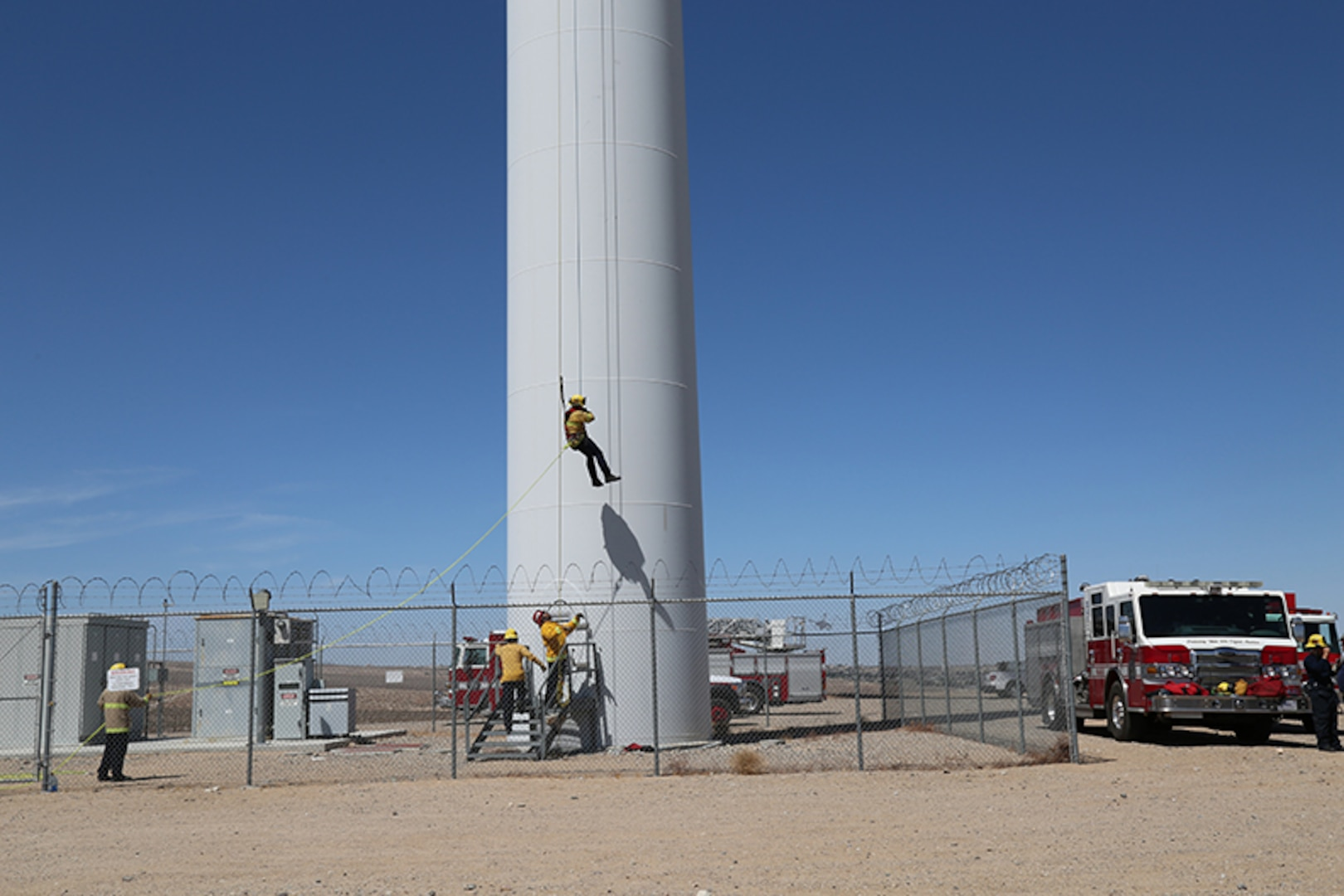 Eric Keck, firefighter/paramedic with Fire and Emergency Services, rappels 230 feet from a wind turbine as part of the Technical Rope Rescue training held aboard Marine Corps Logistics Base Barstow, California, April 15. Captain Tim Yonta, prepares to guide Keck safely to his feet once he reaches the platform below. The training was conducted by Tech Rescue Trainers, Inc. as part of a comprehensive series of technical rescue courses.