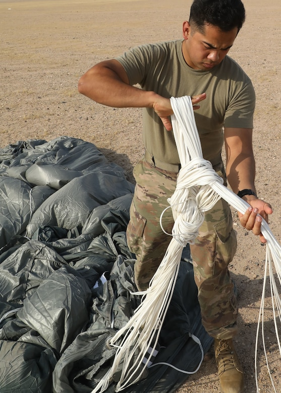 Rigger Spc. Andres Sanchez with the Fort Bragg, North Carolina, based 151st Quartermaster Company, deployed to the U.S. Central Command area of responsibility in support 1st Theater Sustainment Command, collects the rigging lines from one of the four parachutes that successfully carried bundles within 75 meters of the target at the Camp Buehring, Kuwait, drop zone April 22, 2021 using the Joint Precision Air Delivery System, or JPADS. Sanchez said he appreciated the chance to participate in the real-world exercise.