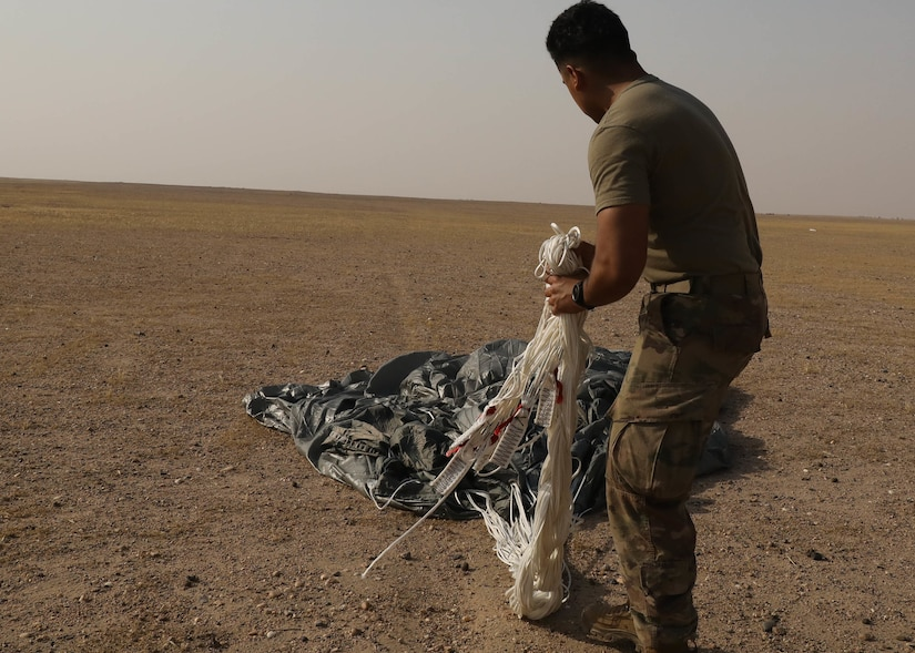 Rigger Spc. Andres Sanchez with the Fort Bragg, North Carolina, based 151st Quartermaster Company, deployed to the U.S. Central Command area of responsibility in support 1st Theater Sustainment Command, collects the rigging lines from one of the four parachutes that each successfully carried bundles within 75 meters of the target at the Camp Buehring, Kuwait, drop zone April 22, 2021 using the Joint Precision Air Delivery System, or JPADS. Sanchez said he appreciated the chance to participate in the real-world exercise.