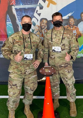 Master Sgt. Daniel Bedford, Air Force Recruiting Service national events program manager, and Chief Master Sgt. Antonio Goldstrom, AFRS command chief, pose for a photo at the AIR RAID QB SIM Experience during the Super Bowl LV Experience outside of Raymond James Stadium in Tampa, Florida, Jan. 31, 2021.