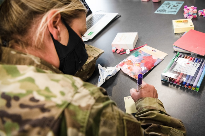 A female Airman writes on a sticky note with a purple marker.