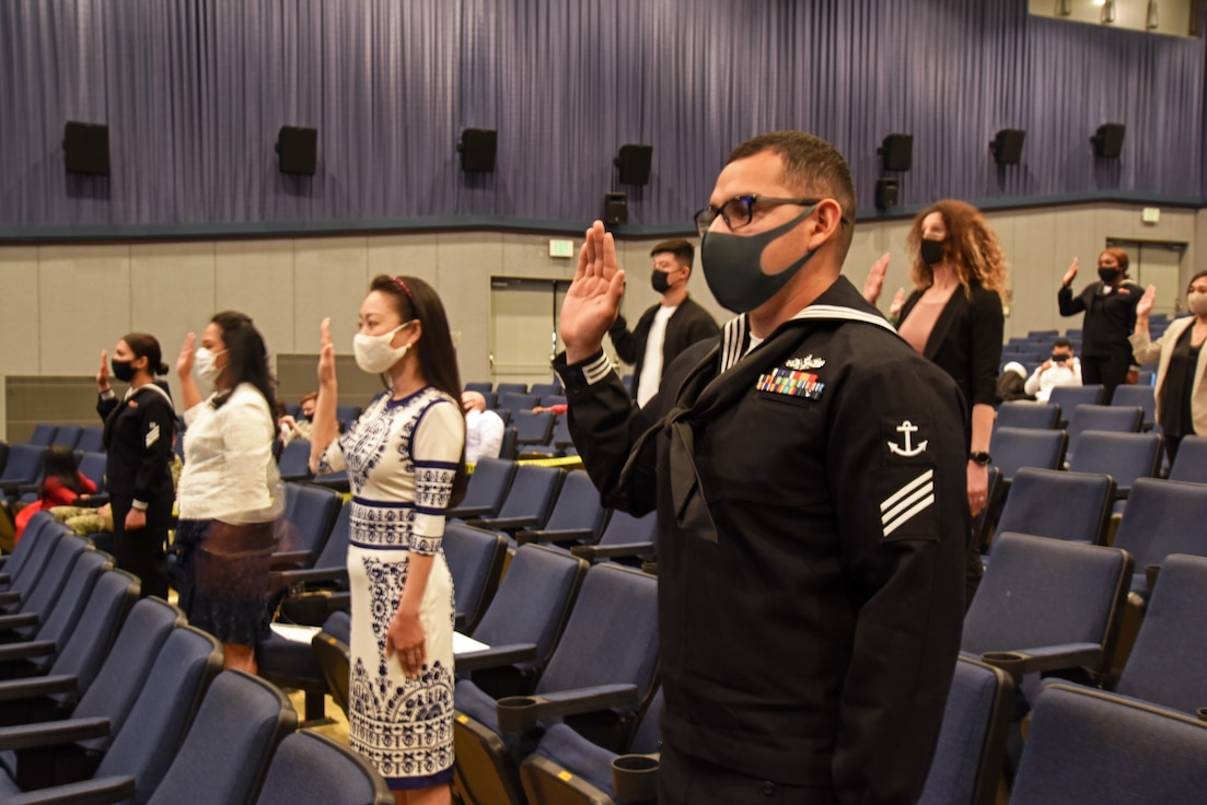 Seaman Armando Diaz-Mejia, right, civilians and fellow Sailors onboard Commander, Fleet Activities Yokosuka (CFAY) recite the Oath of Allegiance during a United States Citizenship and Immigration Services (USCIS) naturalization ceremony hosted by the Region Legal Service Office Western Pacific at Benny Decker Theater.