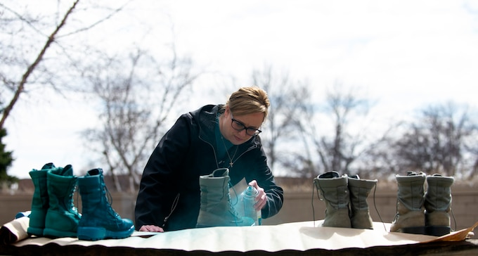 Krista Sheridan, 133rd Sexual Assault Response Coordinator, paints combat boots teal in St. Paul, Minn., Mar. 31, 2021.