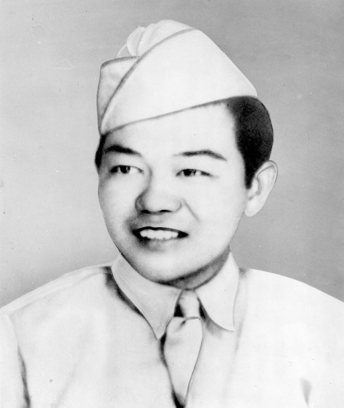 A man in uniform and cap smiles.