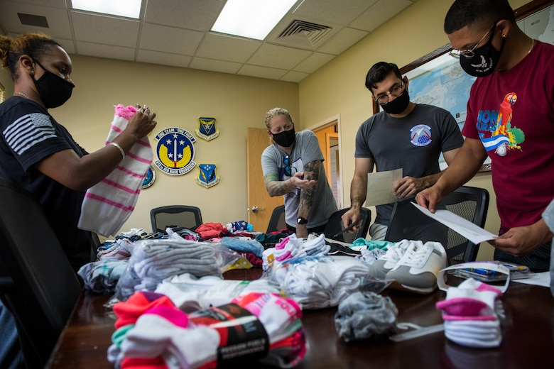 U.S. Airmen with the 612th Air Base Squadron, prepare donations for children at the Children of Love Foundation in La Paz, Honduras, at Soto Cano Air Base, Honduras, April 24, 2021. Members with the 612th ABS donated clothing, shoes, underwear, and towels in a backpack for each child, as well as toys, soap, toothpaste, and school supplies that were delivered in large boxes to 18 orphans who live at the orphanage. (U.S. Air Force photo by Tech. Sgt. Marleah Cabano)