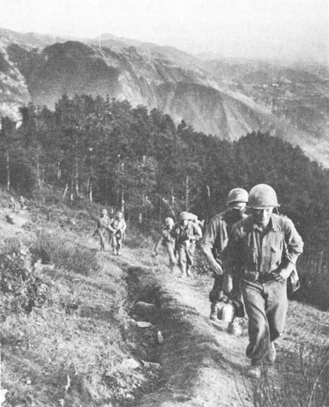Soldiers march in line up a mountainside.