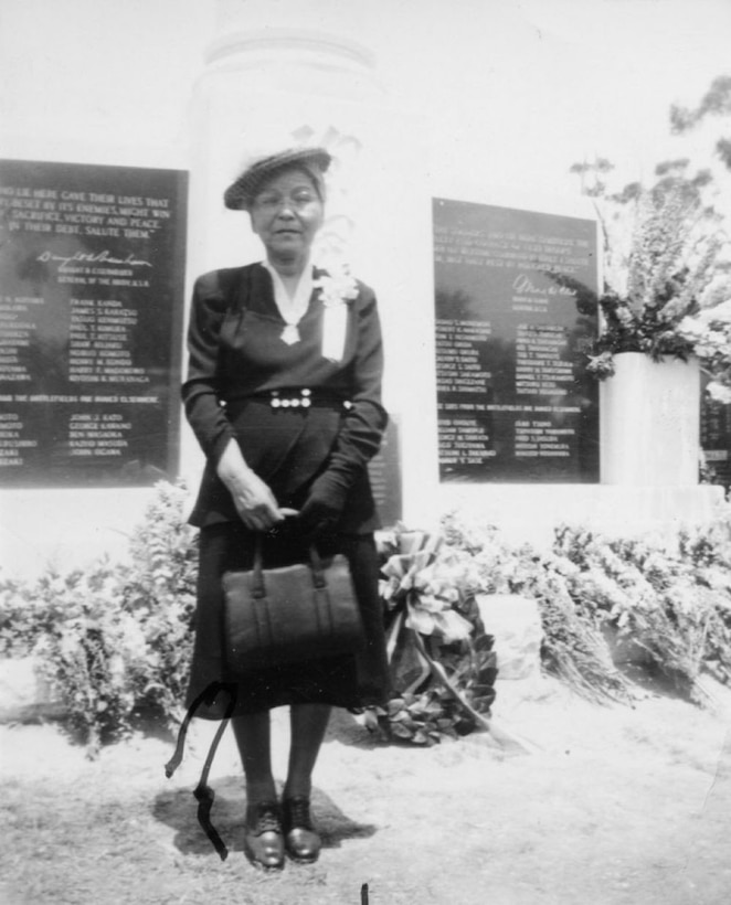 A woman wears a medal on her neck while standing in front of a monument.