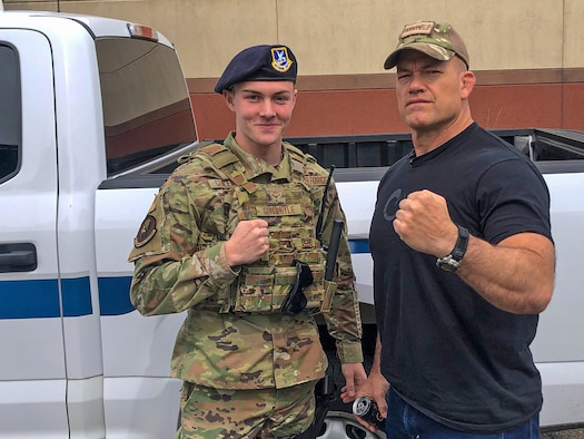 """Man in Air Force duty uniform stands next to posses with John Gretton """"Jocko"""" Willink."""