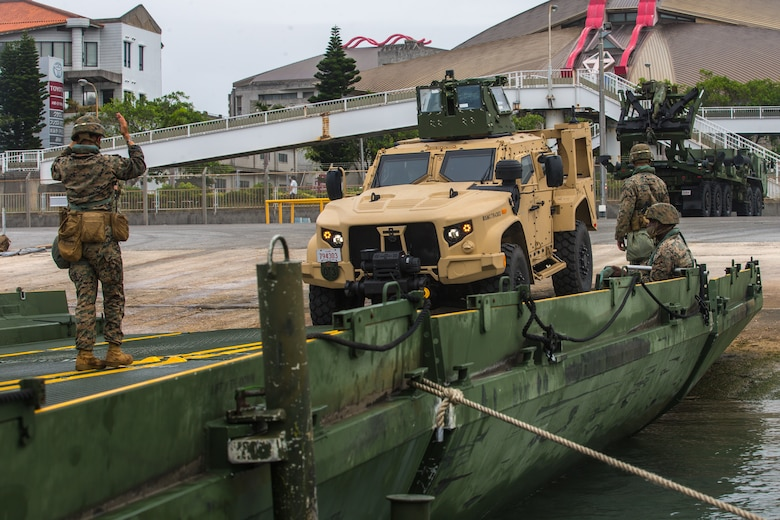 U.S. Marines and Navy Seabees load a Joint Light Tactical Vehicle onto an improved ribbon bridge at Naha Port, April 21.