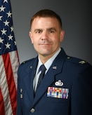 Col. David Black poses in front of a gray field with and American flag behind his right shoulder.