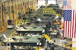 Large building at Marine Depot Maintenance Command, Barstow, California, shows mechanics performing maintenance on a variety of military vehicles.