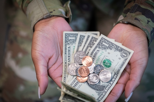 Photo of an Airman holding money