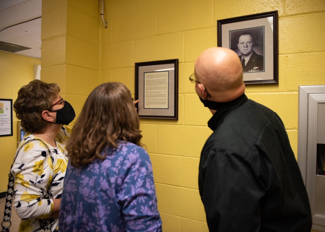 Three individuals look at their father's biography attached to a wall.