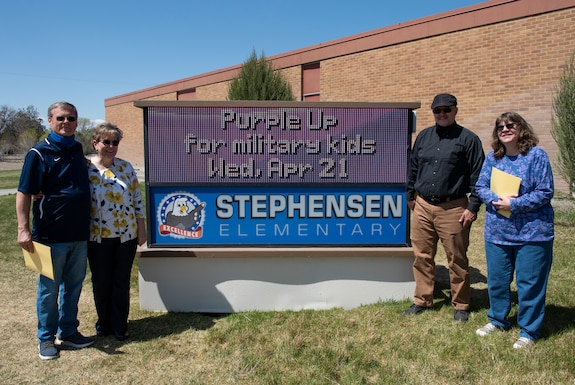 Four individuals stand around the Stephensen Elementary sign and pose for a photo.