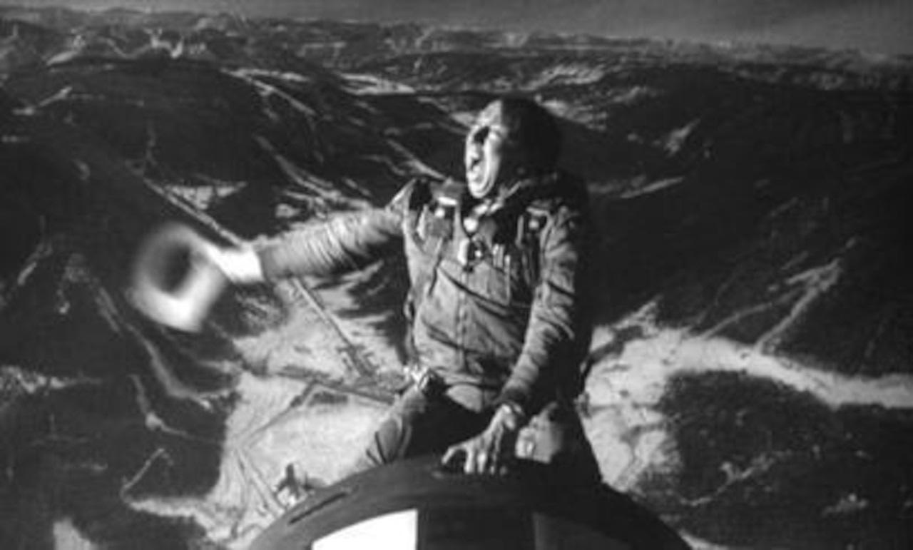 An actor, with a cowboy hat and dressed in a flight suit, rides a bomb.