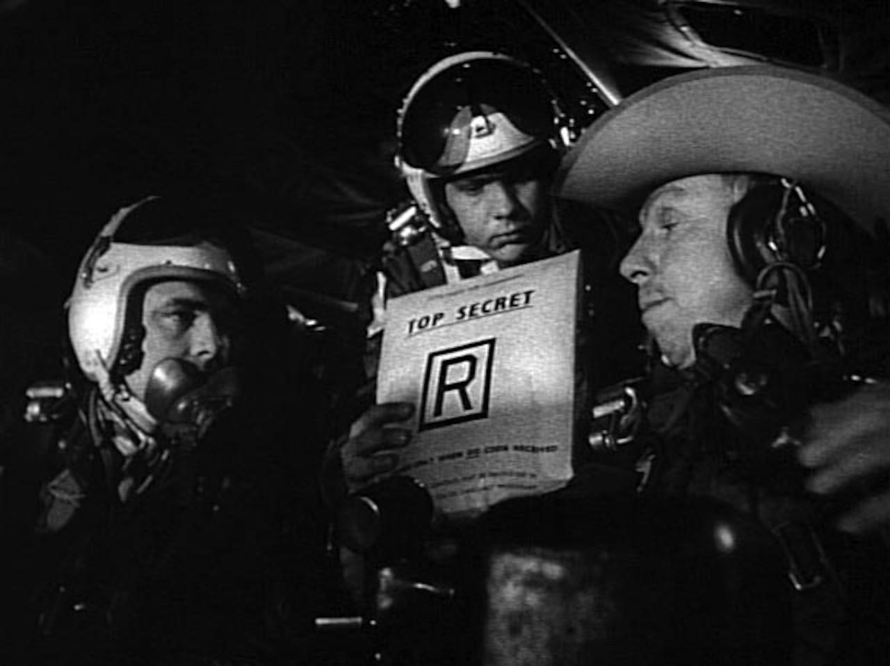Men dressed as military members talk on a movie set.