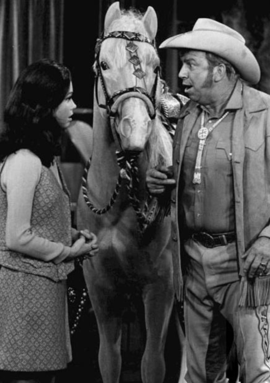 Actors talk on a Western set. There is a horse between them.