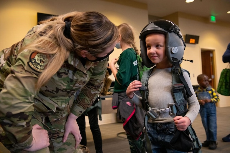 Airman 1st Class Jordyn Eubanks, a 28th Operations Support Squadron aircrew and flight equipment technician, shows Grayson, a military child, how to don aircrew flight equipment at the Kid's Deployment Line event on Ellsworth Air Force Base, S.D., April 17, 2021.