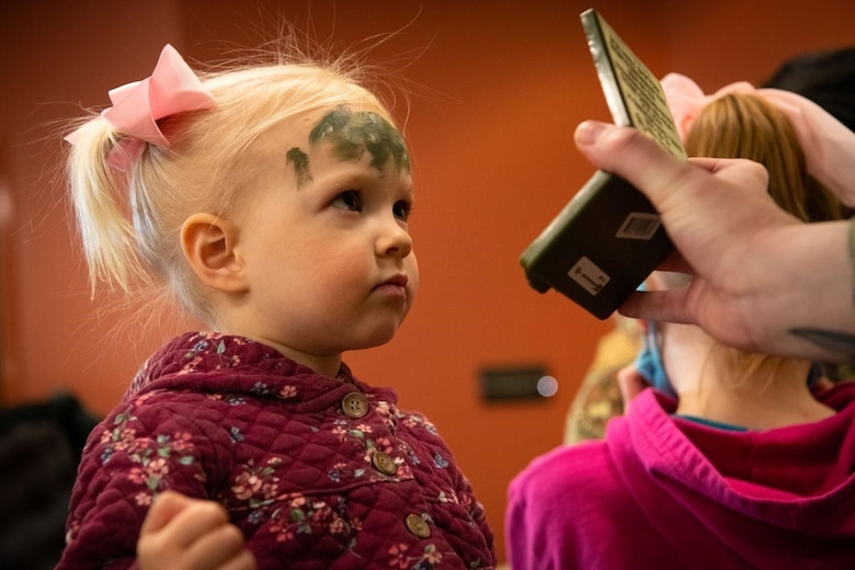 Ennsley, a military child, checks herself in a mirror after having camouflage paint applied to her forehead at the Kid's Deployment Line event on Ellsworth Air Force Base, S.D., April 17, 2021.