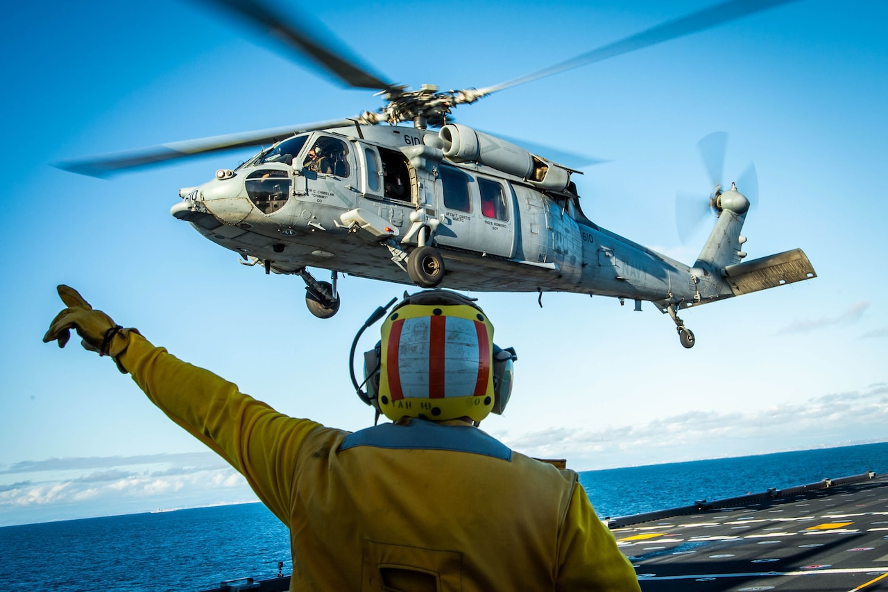 Helicopter hovers over an aircraft carrier.