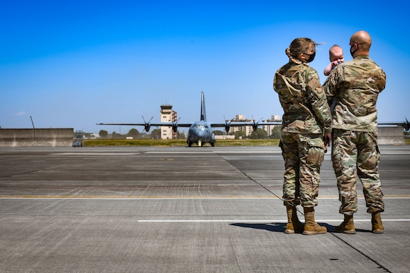 Staff Sgt. Ryann Holzapfel, 374th Airlift Wing Public Affairs craftsman, left, and her husband Staff Sgt. Brendan Miller, Armed Forces Network Tokyo broadcaster, stand on the Yokota flight line with their six-month-old son at Yokota Air Base, Japan, April 26, 2021.