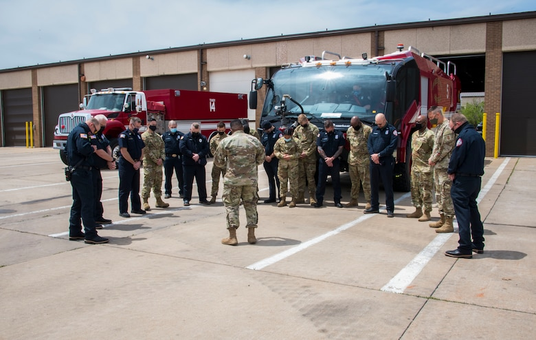Capt. Ladron Thomas, 97th Air Mobility Wing chaplain, prays over Airmen, April 26, 2021, at Altus Air Force Base, Oklahoma. Following tradition, Thomas blessed the firefighters who would operate the truck, emphasizing the truck's ability to assist them while doing their job. (U.S. Air Force photo by Airman 1st Class Amanda Lovelace)
