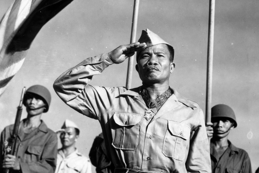 A soldier salutes while wearing a Medal of Honor, as fellow soldiers stand behind him outside and a flag waves above them.