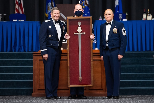 Chief Master Sgt. Robert Tibi, right, Air Force Global Strike Command command first sergeant, presents the Order of the Sword to retired Gen. Robin Rand, left, former AFGSC commander, at Barksdale Air Force Base, Louisiana, April 23, 2021. The Order of the Sword is an Air Force tradition in which members of the enlisted corps recognize and honor senior officers and civilians who have made significant contributions to the welfare and prestige of the enlisted corps. (U.S. Air Force photo by Airman 1st Class Jacob B. Wrightsman)