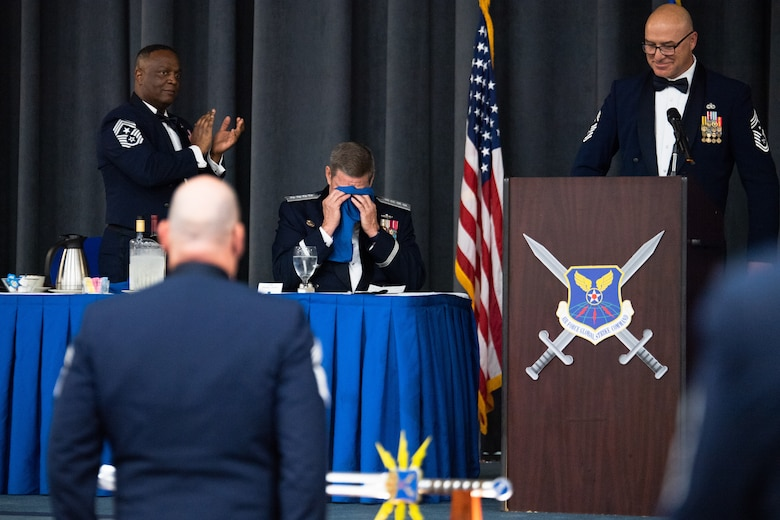 Retired Gen. Robin Rand, former Air Force Global Strike Command commander, wipes tears from his eyes after being honored at an Order of the Sword ceremony at Barksdale Air Force Base, Louisiana, April 23, 2021. The Order of the Sword is an Air Force tradition in which members of the enlisted corps recognize and honor senior officers and civilians who have made significant contributions to the welfare and prestige of the enlisted corps. (U.S. Air Force photo by Airman 1st Class Jacob B. Wrightsman)