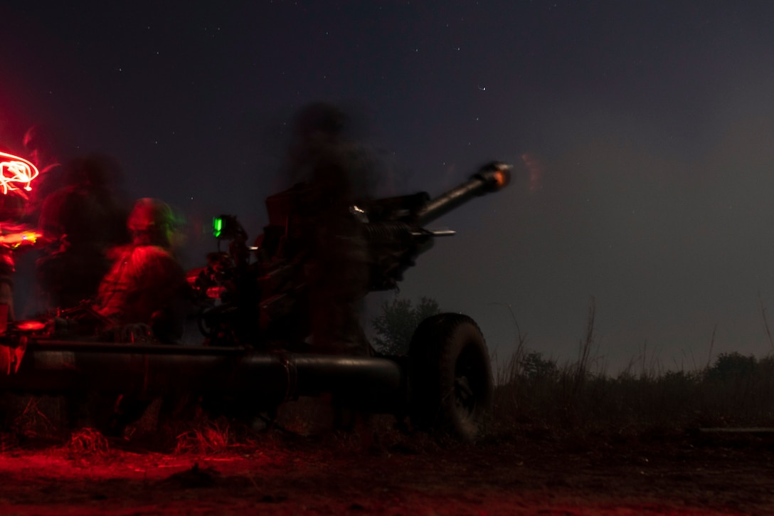 A soldier fires a weapon under a starry sky illuminated by red and green lights.