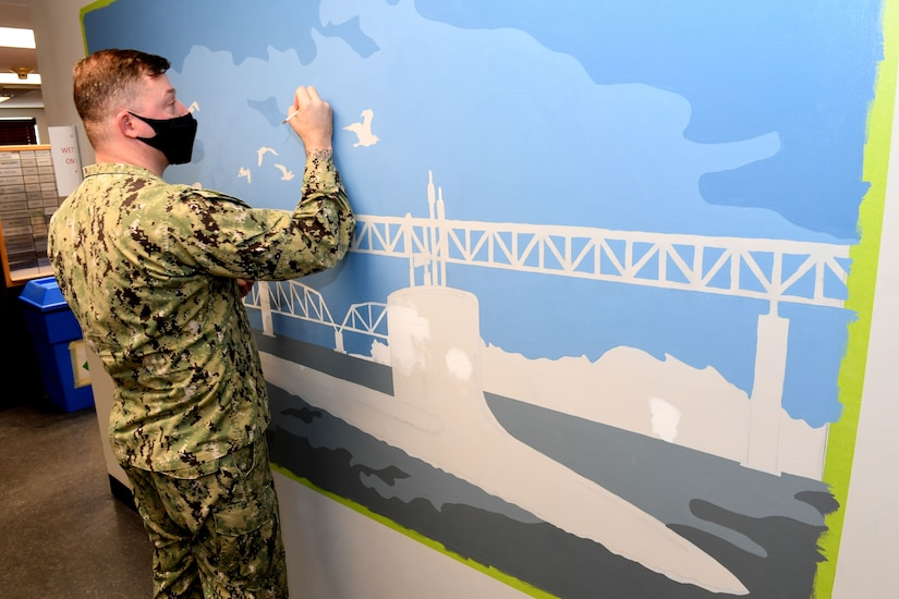 A sailor paints a mural on a wall.