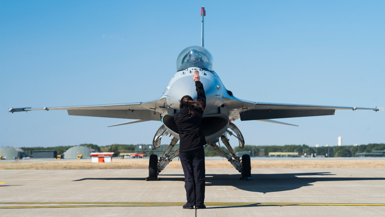Air Force member giving hand signals in front of F-16.